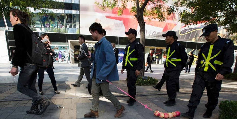 EXPLAINS WHY THEY ARE ESCORTED BY SECURITY GUARDS - Chinese performance artist Han Bing, left, and his friend Hui Li, center, drag an iPhone and a string of apples, respectively, as they are escorted out by security guards of a shopping district after performing outside an Apple retail store in Beijing, China, Thursday, Oct. 16, 2014. Han Bing, known for taking a cabbage out on a walk to raise questions about our attachments to things, hopes to highlight our modern dependence on the mobile phone in this performance.  (AP Photo/Ng Han Guan)