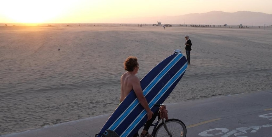 In this Saturday, Sept. 27, 2014 photo a man rides his bicycle while carrying his surfboard along Venice beach section of Los Angeles. The relocation of tech companies to southern California is part of a growing movement of U.S. cities seeking to duplicate the formula that turned northern California's Silicon Valley, slightly south of San Francisco, into a mecca of society-shifting innovation and immense wealth. (AP Photo/Richard Vogel)