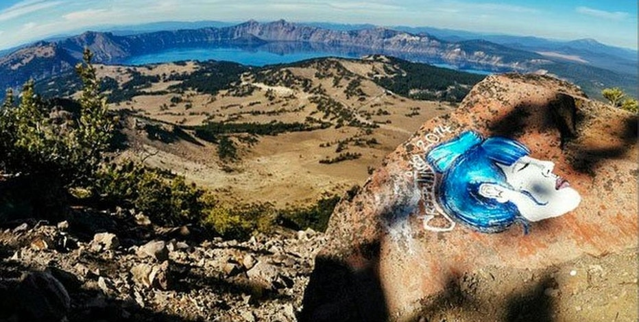 This undated photo taken from an Instagram posting shows an overlook of Crater Lake in Oregon with a rock painting. The National Park Service is investigating paintings and drawings of eerie faces found on rocks across the West in some of the country's most recognizable wilderness areas, including Crater Lake. (AP Photo/Instagram)