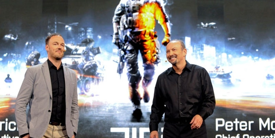 Battlefield 3 executive producer Patrick Bach (L) and Electronic Arts COO Peter Moore unveil Battlefield 3 Premium.
