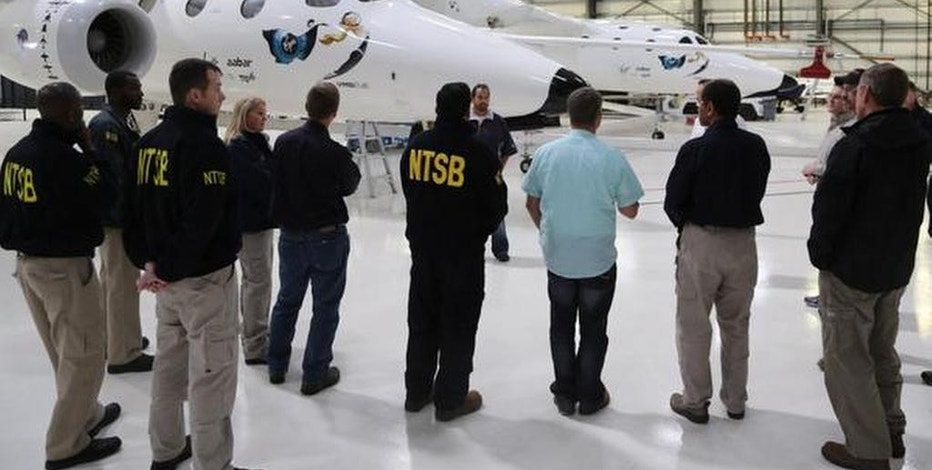 "In this Nov. 2, 2014, photo provided by the National Transportation Safety Board, NTSB investigators stands with the WhiteKnightTwo in Virgin Galactic's hangar in Mojave, Calif. The cause of Friday's crash of Virgin Galactic's SpaceShipTwo has not been determined, but investigators found the ""feathering"" system, which rotates the tail to create drag, was activated before the craft reached the appropriate speed, National Transportation Safety Board Acting Chairman Christopher Hart said. (AP Photo/NTSB)"