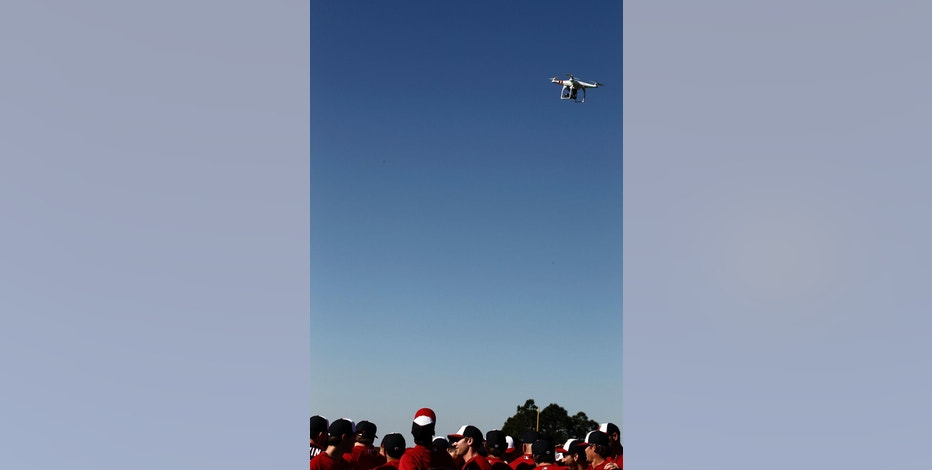 FILE - In this Feb. 17, 2014 file photo, a remote controlled model aircraft flying over the Washington Nationals spring training baseball workout in Viera, Fla. The government is receiving reports nearly every day _ and sometimes two or three times a day _ of drones flying near airplanes and helicopters or close to airports without permission, a sharp increase from just two years ago when such reports were still unusual, federal and industry officials familiar with the reports told The Associated Press.(AP Photo/Alex Brandon, File)