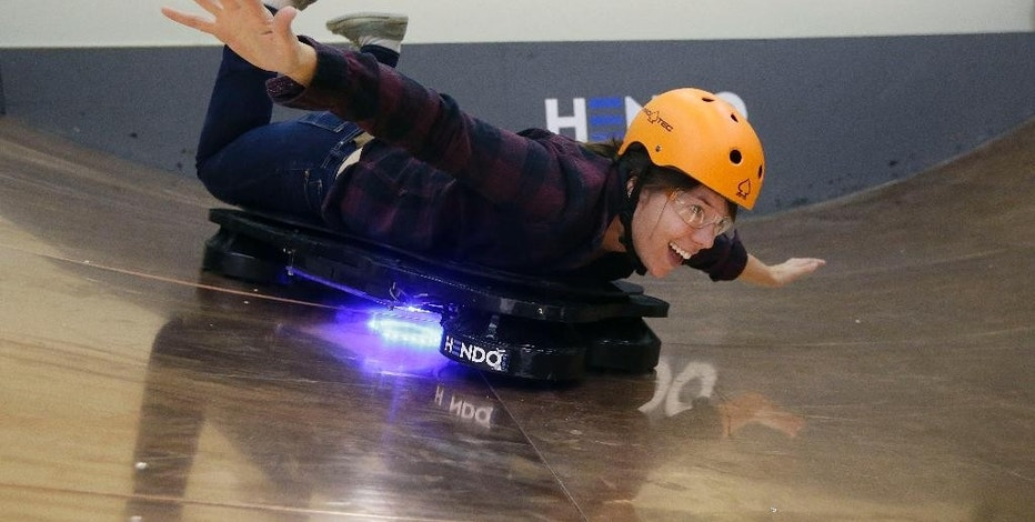 In this Oct. 30, 2014 photo, Arx Pax engineer Shauna Moran demonstrates riding a Hendo Hoverboard in Los Gatos, Calif. Skateboarding is going airborne this fall with the launch of the first real commercially marketed hoverboard which uses magnetics to float about an inch off the ground. (AP Photo/Jeff Chiu)