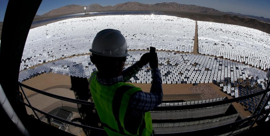 FILE - In this Feb. 11, 2014, file photo, made with an extreme wide-angle lens, Jeff Holland takes a picture of some of the 300,000 computer-controlled mirrors that reflect sunlight to boilers that sit on 459-foot towers at the Ivanpah Solar Electric Generating site in Primm, Nev. The largest solar power plant of its type in the world, promoted as a turning point in green energy, isn't producing the expected energy and one of the reasons is as basic as it gets: The sun isn't shining as often as expected. (AP Photo/Chris Carlson, File)