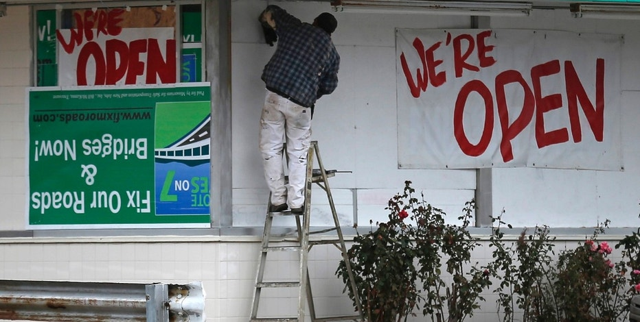 A man works on the exterior of a business in Ferguson, Missouri, November 13, 2014. REUTERS/Jim Young