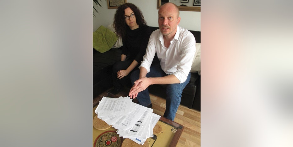 Freelance video journalist Jason Parkinson, 44, and freelance photographer Jess Hurd, 41, gesture at police surveillance files and other documents laid out on their living room table at their home in east London Friday Nov. 21, 2014. The pair are among six British journalists who are suing London's Metropolitan Police and Britainís Home Office over police surveillance of journalists' movements. (AP Photo/Raphael Satter)