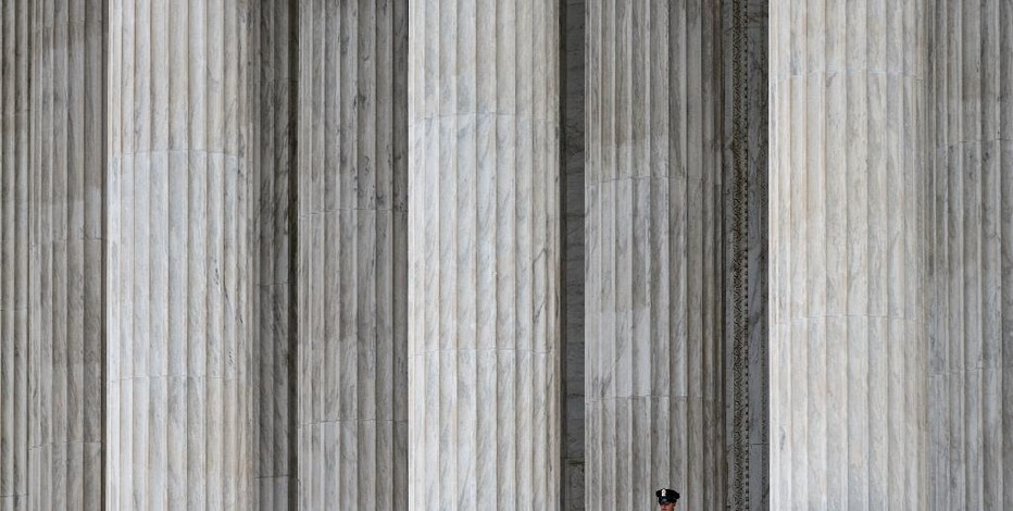 FILE - This Oct. 7, 2014, file photo shows a police officer dwarfed amid the marble columns of the U.S. Supreme Court in Washington. Anthony Elonis claimed he was just kidding when he posted a series of graphically violent rap lyrics on Facebook about killing his estranged wife, shooting up a kindergarten class and attacking an FBI agent. But his wife didn't see it that way. Neither did a federal jury. In a far-reaching case that probes the limits of free speech over the Internet, the Supreme Court on Monday is considering whether Elonis' Facebook posts, and others like it, deserve protection under the First Amendment. (AP Photo/J. Scott Applewhite, File)