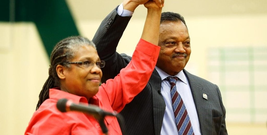 The Rev. Jesse Jackson, right, stands with Trish Dziko, co-founder and executive director of the Technology Access Foundation Academy in Kent, Wash., during an assembly Monday, Dec. 1, 2014. Jackson spoke at length about a grand jury's decision not to indict Ferguson, Missouri police officer Darren Wilson, who is white, for the Aug. 9, 2014 fatal shooting of black 18-year-old Michael Brown and he was in the Seattle area to urge more hiring of minorities by high tech companies such as Amazon and Microsoft. (AP Photo/Ted S. Warren)
