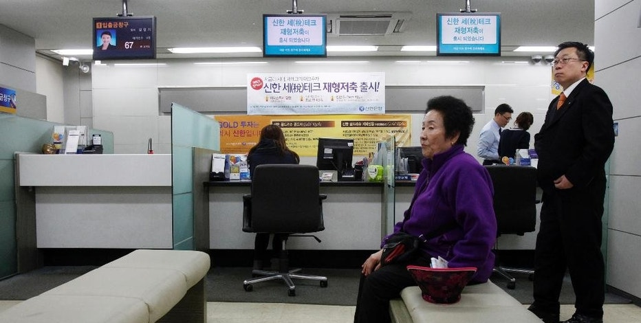 FILE - In this March 20, 2013 file photo, a customer sits in a branch of Shinhan Bank in Seoul, South Korea, after the bank's computer networks was paralyzed. Some cybersecurity experts say they've found striking similarities between the code used in the hack of Sony Pictures Entertainment and attacks blamed on North Korea which targeted South Korean companies last year. Sony has not commented on any Korean connection, except to deny a report Wednesday, Dec. 3, 2014 that it was poised to announce such a link. But three independent researchers told The Associated Press there are intriguing signs of a North Korean link to the attack, even as others warned it's difficult to make a definitive connection. (AP Photo/Ahn Young-joon, File)