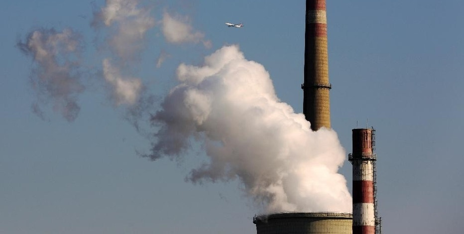 FILE - In this Nov. 13, 2014 file photo, a passenger airliner flies past steams emitted from a coal-fired power plant in Beijing, China. Six countries produce nearly 60 percent of global carbon dioxide emissions. China and the United States combine for more than two-fifths. The planet's future will be shaped by what these top carbon polluters do about the heat-trapping gases blamed for global warming.  (AP Photo/Andy Wong, File)