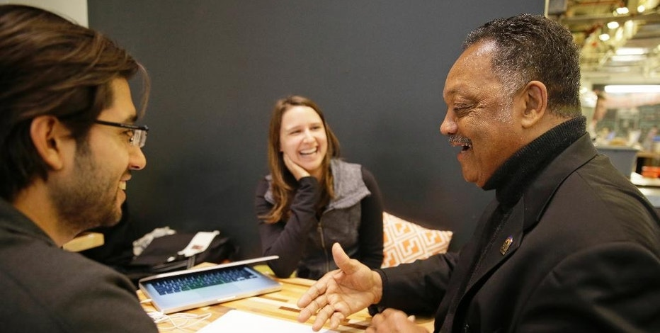 In this photo taken Monday, Dec. 8, 2014, Rev. Jesse Jackson, right, visits Kacie Gonzalez, vice president of business development, center, and Nick Norena, both with the company Shoto, at the Workshop Cafe in San Francisco. Now that Jackson and, his group, Rainbow Push, have gotten the technology industry's biggest companies  to confront an embarrassing shortage of women, African-Americans and Hispanics on their payrolls, he is stepping up the pressure to come up with solutions at workshop to be held Wednesday in Silicon Valley. (AP Photo/Eric Risberg)