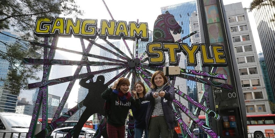 """In this Wednesday, Nov. 26. 2014 photo, Japanese tourists take picture in front of a structure to advertising South Korean rapper PSY's """"Gangnam Style"""" at the Gangnam district in Seoul, South Korea. Gangnam has a special significance in South Korea as the place where a globalized youth culture emerged from a generation that had opportunities to travel and study abroad. The present day Gangnam is still seen as the place that brings foreign culture and ideas to the rest of the country. (AP Photo/Ahn Young-joon)"""
