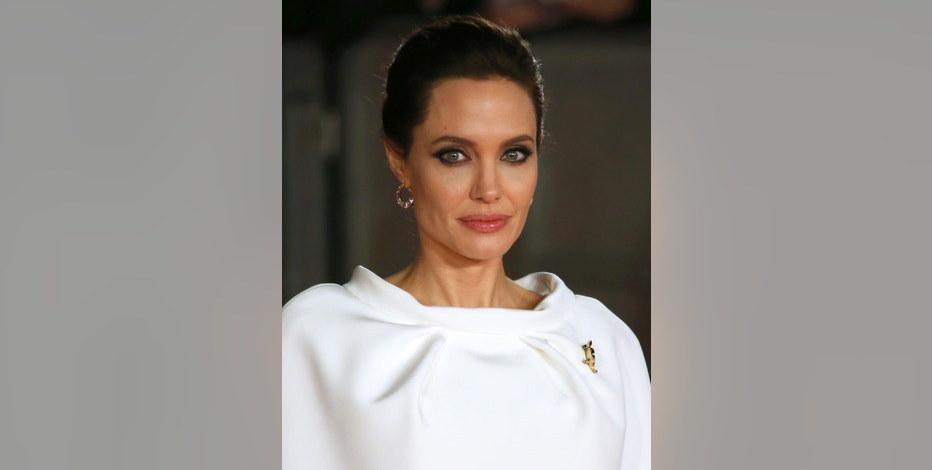 """FILE - In this Nov. 25, 2014 file photo, director Angelina Jolie poses for photographers upon arrival at the premiere of the film """"Unbroken"""" in London. Scott Rudin, the high-powered producer at the center of the latest embarrassment stemming from the Sony hacking scandal, has apologized for remarks he made in leaked emails. In the series of private emails obtained by Gawker and Buzzfeed this week, Rudin, corresponding with Sony Pictures Entertainment co-chairman Amy Pascal, called """"Unbroken"""" director Angelina Jolie a """"spoiled brat"""" and made jokes about President Barack Obama's race and presumed taste in movies. (Photo by Joel Ryan/Invision/AP, File)"""