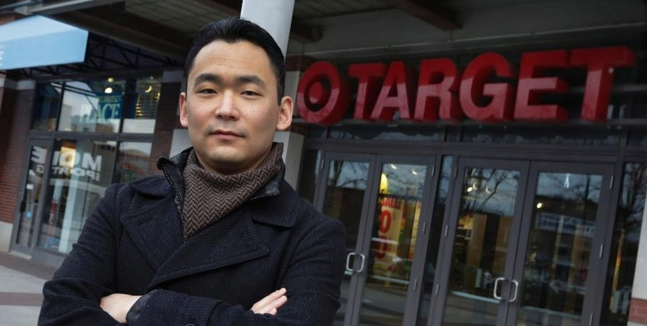 In this Dec. 2, 2014 file photo, identity theft victim Mark Kim poses for photos in front of a Target store, in the Brooklyn borough of New York. Kim spent seven months trying to clear his credit history after his personal information was compromised in a data breach at Target last year.  (AP Photo/Richard Drew)