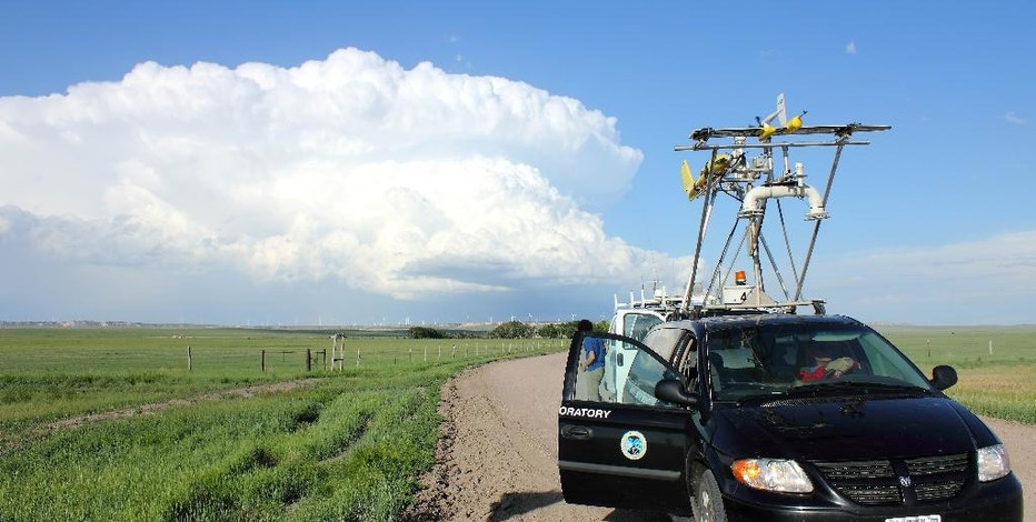 This June 15, 2013 photo, made available courtesy Sean Waugh, NOAA, shows a team of researchers from the University of Colorado and NOAA sampling surface boundaries in the Pawnee National Grasslands, near Grover, Colo. as a storm develops over Wyoming. Colorado and Nebraska researchers say they've collected promising weather data by flying instrument-laden drones into big storms, and now they want to expand the project in hopes of learning how tornados form. (AP Photo/Sean Waugh, NOAA)