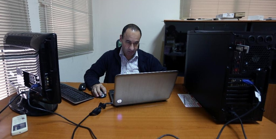 WITH STORY MIDEAST ISLAMIC STATE CYBERATTACK BY RAPHAEL SATTER - In this photo dated Wednesday, Dec. 17, 2014, Lebanese Bahaa Nasr of Cyber Arabs checks his email from his office in Beirut, Lebanon.  Cyber Arabs is an online safety project run by the London-based Institute for War and Peace Reporting and Nasr is among those who recently helped uncover a botched cyberattack suspected of having been carried out by the Islamic State group. (AP Photo/Bilal Hussein)