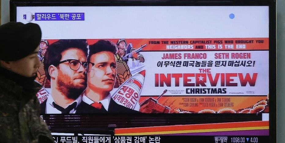 """FILE - In this Dec. 22, 2014, file photo, a South Korean army soldier walks near a TV screen showing an advertisement of Sony Picture's """"The Interview,"""" at the Seoul Railway Station in Seoul, South Korea.  It seems everyone has a theory about who really hacked Sony Pictures Entertainment Inc. Despite President Barack Obama's conclusion that North Korea was the culprit, the Internet's newest game of whodunit continues. Top theories include disgruntled Sony insiders, hired hackers, other foreign governments or Internet hooligans. Even some experts are undecided, with questions about why the communist state would steal and leak gigabytes of data, email threats to some Sony employees and their families then threaten moviegoers who planned to watch """"The Interview"""" on Christmas. (AP Photo/Ahn Young-joon, File)"""
