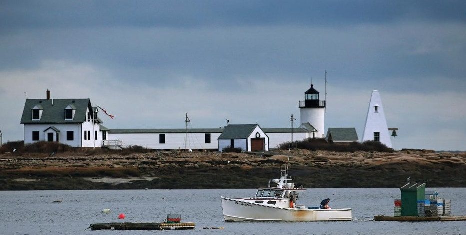 In this Monday, Dec. 22, 2014 photo, a lobster boat passes by the Goat Island Light at Cape Porpoise in Kennebunkport, Maine. Earlier this year the Coast Guard replaced the lighthouse's old foghorn at the with an on-demand foghorn that mariners can activate with a marine radio. The move has drawn considerable criticism from the land trust that owns the island. (AP Photo/Robert F. Bukaty)
