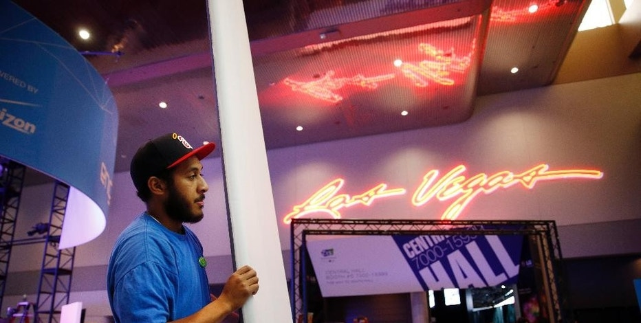 John Fifita helps build a booth in preparation for International CES at the Las Vegas Convention Center on Sunday, Jan. 4, 2015, in Las Vegas. The International CES convention starts Tuesday. (AP Photo/John Locher)