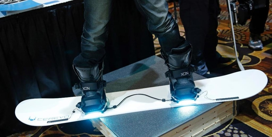 Takuma Iwasa demonstrates the Cerevo XON Snow-1 snowboard bindings at CES Unveiled, a media preview event for CES International, Sunday, Jan. 4, 2015, in Las Vegas. The bindings have pressure sensors to analyze your snowboarding technique. (AP Photo/John Locher)