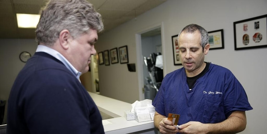 In this Jan. 5, 2015 photo, Dr. Greg Werner, right, takes a credit card payment from Michael Cox using a Square device attached to a smart phone at his office in New York. The chiropractor ditched his traditional credit card reader for Square four years ago to save money. (AP Photo/Seth Wenig)
