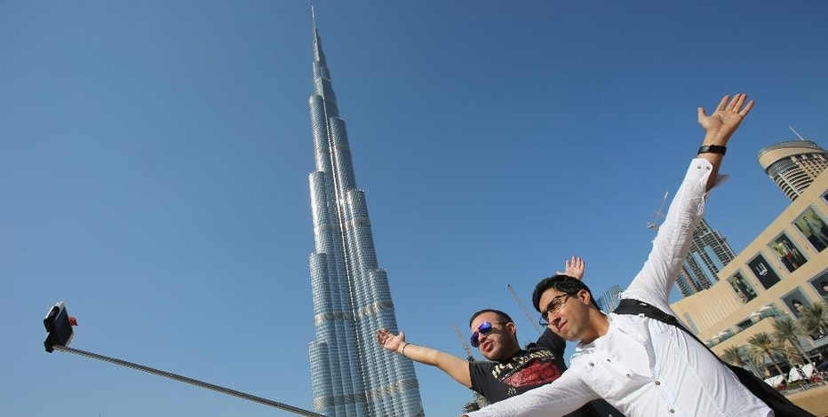 """In this Tuesday, Jan. 6, 2015 photo, Rasul Alekberov holds a selfie stick next to his friend Gudrat Aghayev both tourists from Republic of Azerbaijan while they take a selfie in front of """"Burj Khalifa"""", world's tallest tower in Dubai, United Arab Emirates. Selfie sticks have become popular among tourists because you don't have to ask strangers to take your picture, and you can capture a wide view in a selfie without showing your arm. (AP Photo/Kamran Jebreili)"""