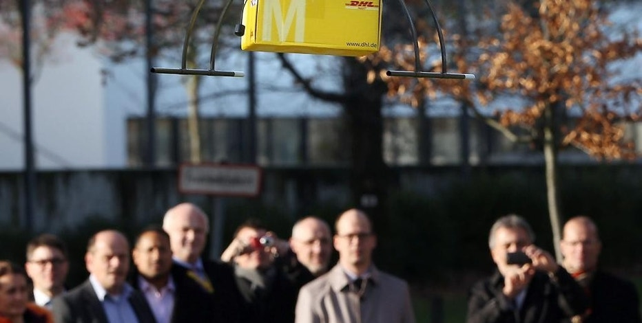 In this Dec. 9, 2013 photo, a Deutsche Post DHL drone carrying a small parcel flies in front of journalists during a demonstration in Bonn, Germany. Germany's express delivery and mail company is testing a drone that could be used to deliver urgently needed goods to hard-to-reach places. The aircraft can carry up to 3 kilograms (6.6 pounds).  (AP Photo/dpa, Oliver Berg)