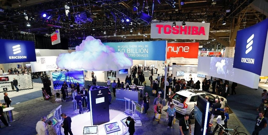 People walk through the Ericsson booth during the International CES Friday, Jan. 9, 2015, in Las Vegas. (AP Photo/John Locher)