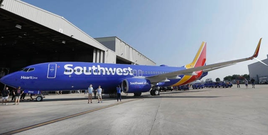 A Southwest Airlines plane sporting the newly unveiled paint color scheme sits outside a hanger after an event at Love Field Monday, Sept. 8, 2014, in Dallas. The change comes in a year during which 43-year-old Southwest has begun international flights, expanded in New York and Washington, and is freed from longtime government limits on its Dallas schedule. (AP Photo/LM Otero)