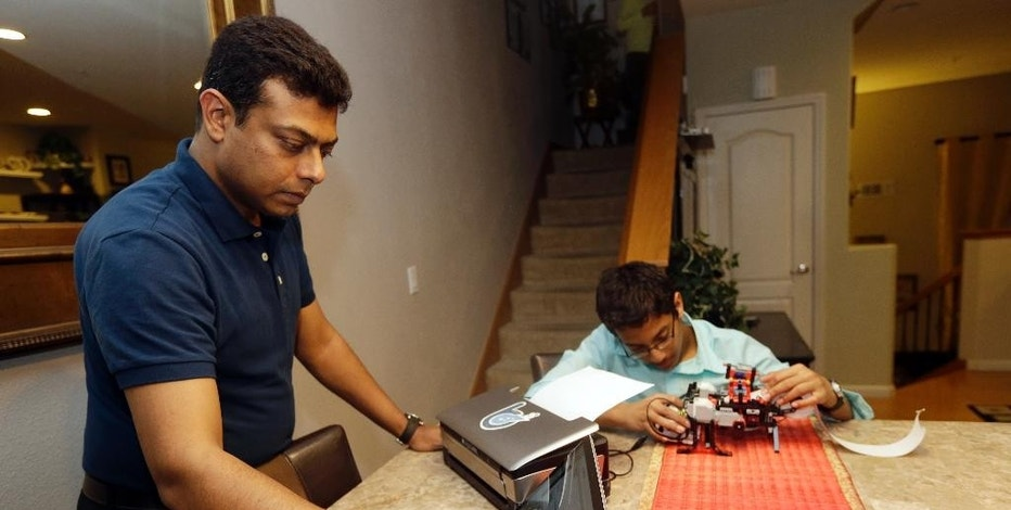 Shubham Banerjee, right, works on his lego robotics braille printer as his dad Neil sets up a current computer version of the printer at home Tuesday, Jan. 6, 2015, in Santa Clara, Calif.  Banerjee launched a company to develop a low-cost machine to print Braille materials for the blind. It's based on a prototype he built with his Lego robotics kit for a school science fair project. Last month, tech giant Intel Corp. invested in his startup, Braigo Labs, making the 8th grader the youngest entrepreneur to receive venture capital funding. (AP Photo/Marcio Jose Sanchez)