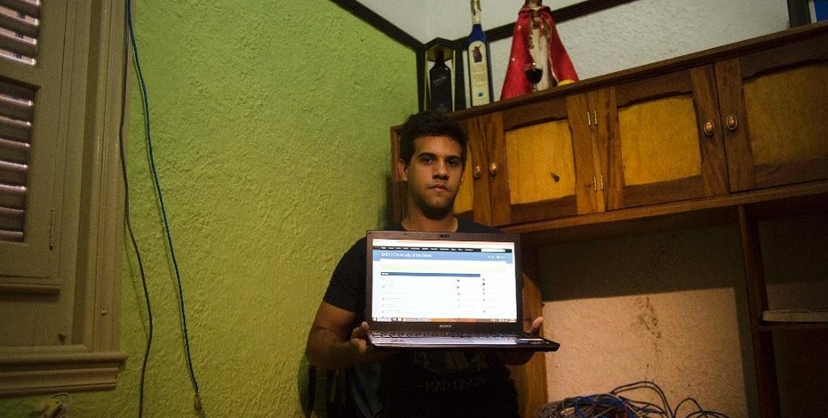 In this Jan. 4, 2015 photo, Rafael Antonio Broche Moreno poses with his computer, modem and intranet network cabling at his home in Havana. Cut off from the Internet, Cuban youth have quietly linked thousands of computers into a hidden network that stretches miles across Havana, letting them chat with friends, play games and download hit movies in a mini-replica of the online world that most Cubans can't access. (AP Photo/Ramon Espinosa)