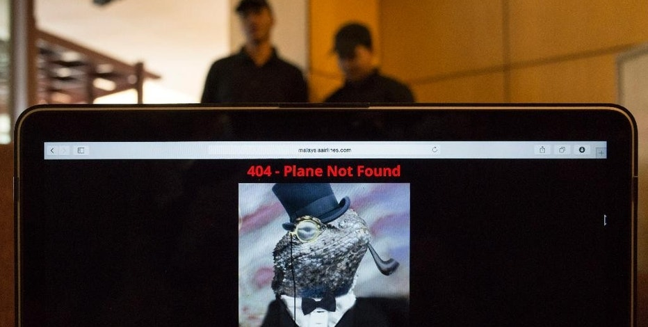 """Workers stand behind a computer which shows the hacked website of Malaysia Airlines, at a cafe in Petaling Jaya outside Kuala Lumpur, Malaysia, Monday, Jan. 26, 2015. The airline's site was changed on Monday, at first with a message saying """"404 - Plane Not Found"""" and that it was """"Hacked by Cyber Caliphate."""" The browser tab for the website said """"ISIS will prevail."""" (AP Photo/Joshua Paul)"""