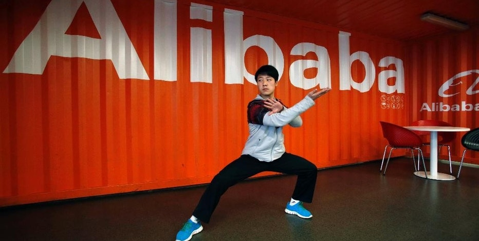 FILE - In this March 26, 2013 file photo, a worker demonstrates martial arts during an open day at the Alibaba Group office in Hangzhou in east China's Zhejiang province. For years, Alibaba faced complaints it failed to stamp out sales of counterfeit goods on its e-commerce websites. But Chinese regulators stayed silent, apparently reluctant to disrupt the rise of an Internet star even as they accused foreign automakers, dairies and others of violating anti-monopoly or consumer protection rules. That honeymoon ended this week, the last week of January 2015. In a stinging report, a Cabinet agency accused Alibaba Group Ltd. of allowing sales of fake goods and hurting consumers. (AP Photo/File) CHINA OUT