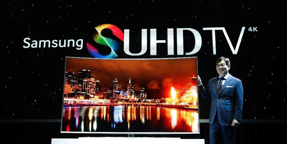 Kim Hyun-seok, head of Samsung Electronics' TV business, poses with its SUHD 4K TV during a press conference in Seoul, South Korea, Thursday, Feb. 5, 2015. South Korean electronics giant Samsung Electronics Co. has started domestic sales of high-end televisions powered by its Tizen operating system and plans to add washing machines, fridges and other appliances to the range of products that use the software.(Ahn Young-joon)