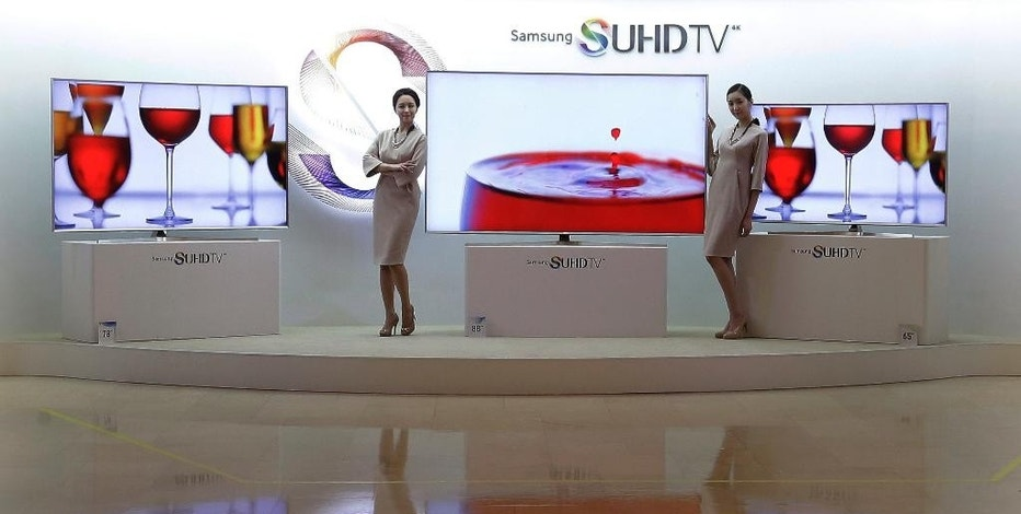 Models pose with Samsung Electronics Co.'  SUHD 4K TVs during a press conference in Seoul, South Korea, Thursday, Feb. 5, 2015. South Korean electronics giant Samsung Electronics Co. has started domestic sales of high-end televisions powered by its Tizen operating system and plans to add washing machines, fridges and other appliances to the range of products that use the software.(Ahn Young-joon)
