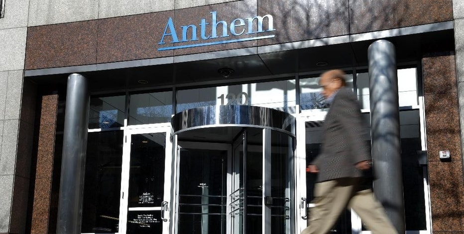 A man walks past health insurer Anthem's corporate headquarters in Indianapolis, Thursday, Feb. 5, 2015. Hackers broke into the company's database storing information for about 80 million people in an attack bound to stoke fears many Americans have about the privacy of their most sensitive information. (AP Photo/Michael Conroy)