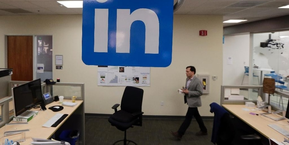 In this Nov. 6, 2014 photo, a LinkedIn employee walks past a company logo at the company's headquarters in Mountain View, Calif. LinkedIn reports quarterly financial results on Thursday, Feb. 5, 2015. (AP Photo/Marcio Jose Sanchez)