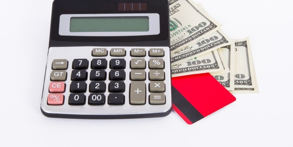 Credit card, one hundred dollar banknotes and calculator, isolated on white background.