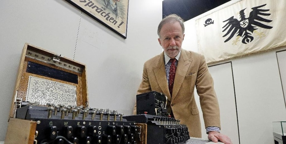 "Kenneth Rendell, founder and director of the World War II Museum, poses with Nazi Enigma encryption machines on display in Natick, Mass., Wednesday, Feb. 18, 2015. In the Oscar-nominated film ""The Imitation Game,"" Benedict Cumberbatch leads a code-breaking operation targeting the Nazis' infamous Enigma encryption machines. Rendell says his museum boasts the largest U.S. collection of Enigmas outside of the NSA. (AP Photo/Elise Amendola)"