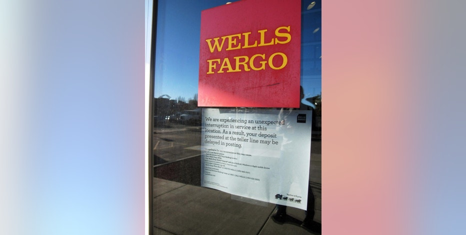 A sign posted outside the Wells Fargo bank in Flagstaff, Ariz., Wednesday, Feb. 25, 2015, warns customers that deposits might not be posted to their accounts immediately because of an Internet and phone outage. (AP Photo/Felicia Fonseca)