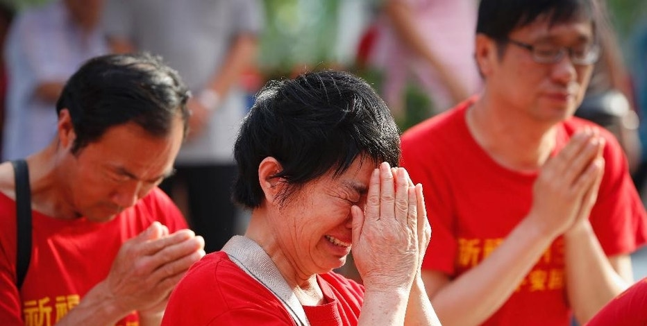 Chinese family members of passengers on board the missing Malaysia Airlines Flight 370 cries as they pray at a temple in Kuala Lumpur, Malaysia, Sunday, March 1, 2015. Australia, Indonesia and Malaysia will lead a trial to enhance the tracking of aircraft over remote oceans, allowing planes to be more easily found should they vanish like Malaysia Airlines Flight 370, Australia's transport minister said Sunday. The announcement comes one week ahead of the anniversary of the disappearance of Flight 370, which vanished last year on a flight from Kuala Lumpur to Beijing with 239 people on board. No trace of the plane has been found. (AP Photo/Vincent Thian)
