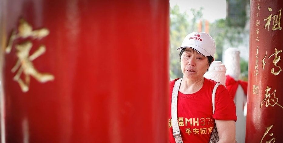A Chinese family member of a passenger on board the missing Malaysia Airlines Flight 370, cries after praying at a temple in Kuala Lumpur, Malaysia,Sunday, March 1, 2015. Australia, Indonesia and Malaysia will lead a trial to enhance the tracking of aircraft over remote oceans, allowing planes to be more easily found should they vanish like Malaysia Airlines Flight 370, Australia's transport minister said Sunday. The announcement comes one week ahead of the anniversary of the disappearance of Flight 370, which vanished last year on a flight from Kuala Lumpur to Beijing with 239 people on board. No trace of the plane has been found. (AP Photo/Vincent Thian)