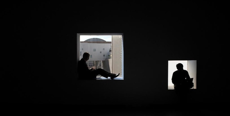 Visitors sit as they work with their computers during the Mobile World Congress Wireless show, the world's largest mobile phone trade show, in Barcelona, Spain, Tuesday, March 3, 2015. (AP Photo/Manu Fernandez)