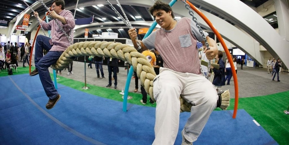 Phillip Chu Joy, left, and Juan Pablo Cabrejos Meza, right, ride a swing in the Biba smart playground at the Game Developers Conference, Wednesday, March 4, 2015, in San Francisco. (AP Photo/Eric Risberg)