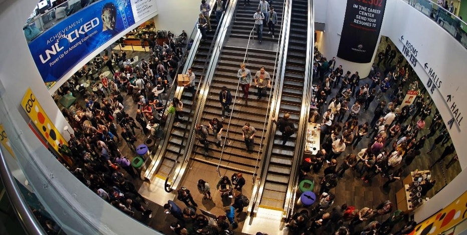 People line up and make their way to the opening of the exhibit hall at the Game Developers Conference, Wednesday, March 4, 2015, in San Francisco. (AP Photo/Eric Risberg)