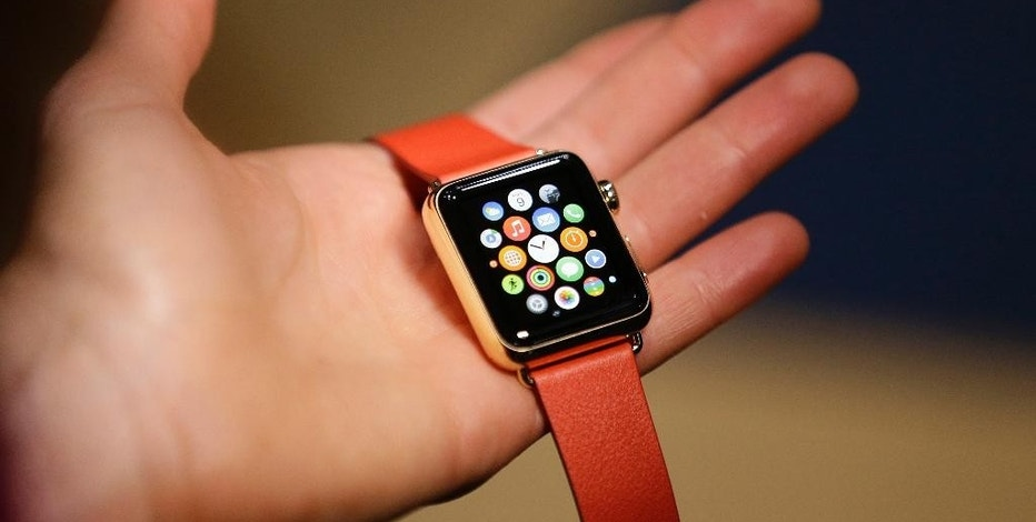 A woman holds the Apple Watch Edition during a demo following an Apple event Monday, March 9, 2015, in San Francisco. Make calls, read email, control music, manage Instagram photos, keep up with your workout, pay for groceries, open your hotel room door. CEO Tim Cook says you can do it all from your wrist with Apple Watch — for 18 hours a day. That's how long the battery will last on an average day. (AP Photo/Eric Risberg)