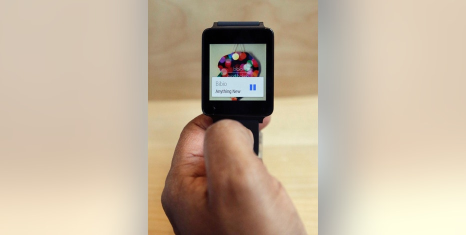 FILE - In this June 25, 2014 file photo, a man looks at the LG G Watch, an Android Wear smartwatch, on the demo floor at Google I/O 2014 in San Francisco. (AP Photo/Jeff Chiu, File)