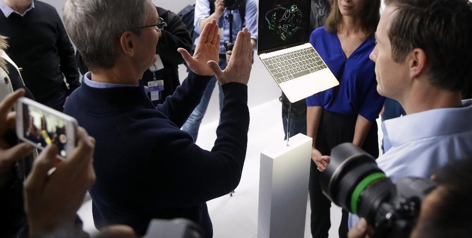 Apple CEO Tim Cook, left, and Christy Turlington Burns, second from right, look at the new Apple Macbook in the demo room after the Apple event on Monday, March 9, 2015, in San Francisco.  The new computer weighs just two pounds and the company says it's the world's most energy-efficient laptop. (AP Photo/Eric Risberg)