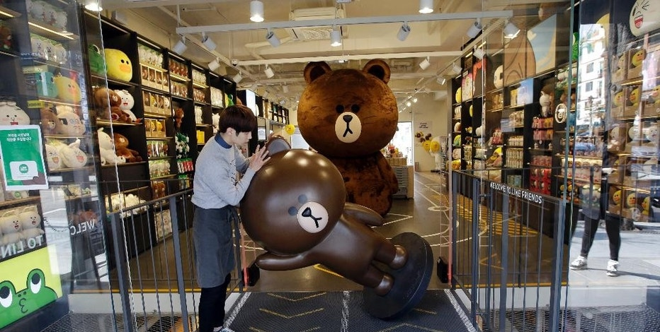 """In this March 16, 2015, an employee carries a human-size cutout Line's character Brown bear, to place outside the door at the Line Friends flagship shop in Seoul, South Korea. For smartphone users in Asia where most of Line's 181 million monthly users are located, the characters are as familiar as Hello Kitty or Disney's animated stars. They are not well known in America or Europe but owner Line Corp. hopes to change that. It plans to open 100 stores selling Brown dolls and other cute """"Line Friends"""" paraphernalia worldwide over the next three years as a way to draw more users to the app. (AP Photo/Lee Jin-man)"""