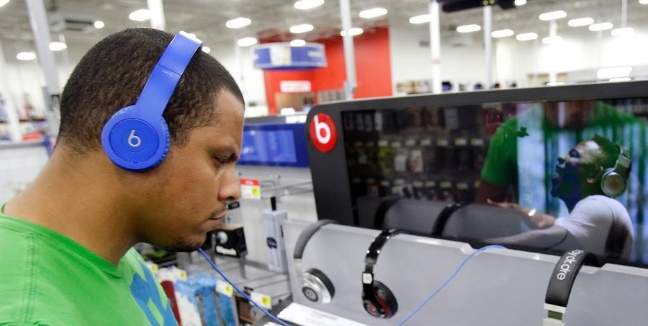 FILE - In this May 28, 2014 file photo, Eric Soriano listens to music with a pair of Beats headphones at a Best Buy store in Orlando, Fla. With paid subscriptions to music streaming services like Beats Music, Spotify, Pandora and others, you can listen to as many songs as you want on a variety of personal computers, phones, tablets and other devices. (AP Photo/John Raoux)